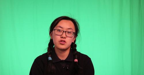 Student facing camera with green screen behind.